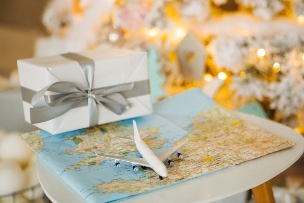Toy airplane sitting on top of a paper map with a gift box