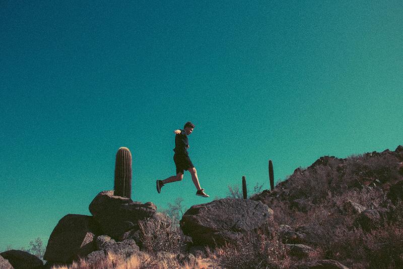 Person jumping between rocks in the desert near Phoenix