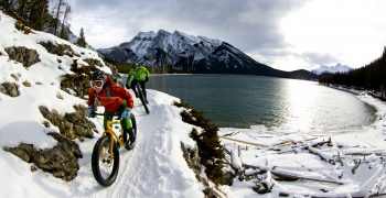 Friends mountain biking at a snowy destination
